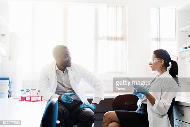 chemist discussing with colleague at laboratory - leanintogether stock pictures, royalty-free photos & images