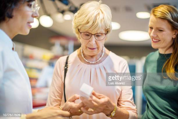 chemist explaining medication to customers - german short haired pointer stock pictures, royalty-free photos & images