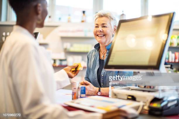chemist giving the card to costumer after the payment - pharmacy stock pictures, royalty-free photos & images