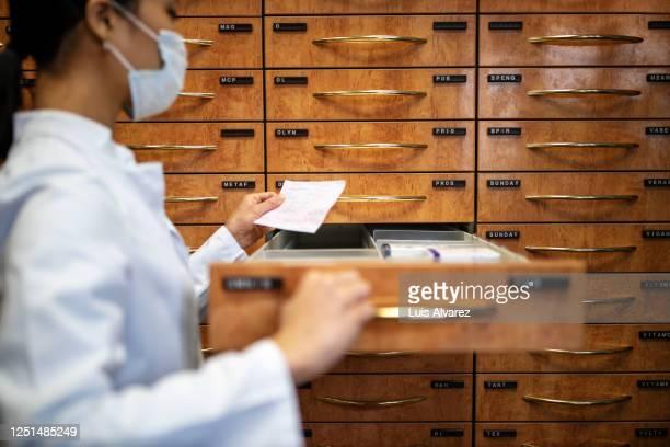 chemist looking for prescription medication in shelf at pharmacy - lagerraum stock-fotos und bilder