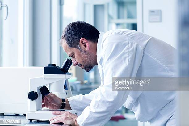 Chemist looking through microscope at a laboratory