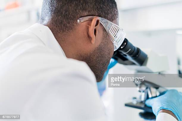 Chemist looking through microscope at laboratory
