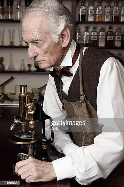 Chemist pondering findings next to microscope