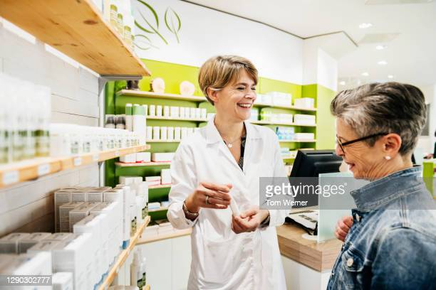 chemist smiling while assisting mature customer in pharmacy - german short haired pointer stock pictures, royalty-free photos & images