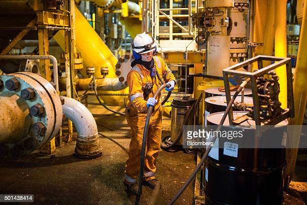 A chemist uses equipment to access chemicals from a barrel on the well deck of the Armada gas condensate platform operated by BG Group Plc in the...