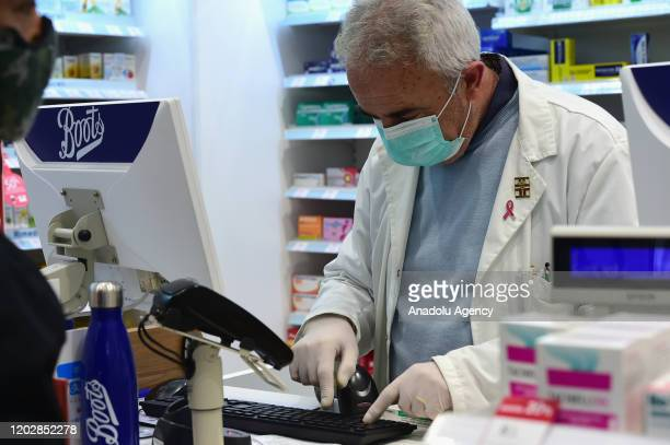 A chemist wears a respiratory mask while working in a pharmacy on February 23 2020 in Milan Italy The Lombardy is one of the most affected region in...