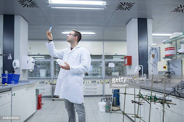 Chemist working in lab looking at test tube
