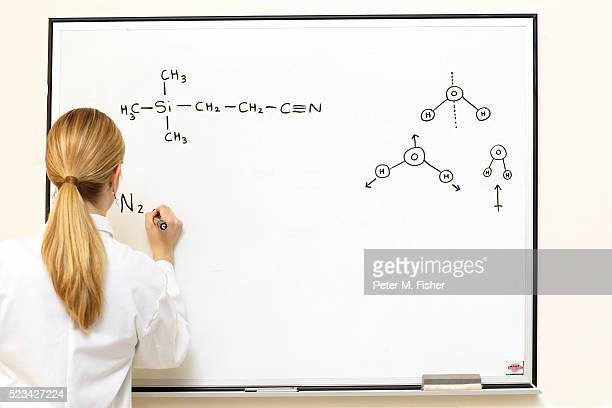 chemistry student writing on a whiteboard - chemical formula stock pictures, royalty-free photos & images