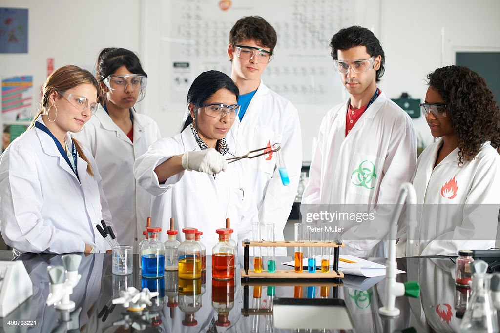 Chemistry teacher and students doing experiment : Stock Photo