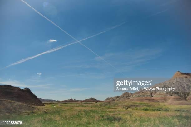 chemtrails / vapor trails above the badlands in south dakota - chemtrails stock-fotos und bilder
