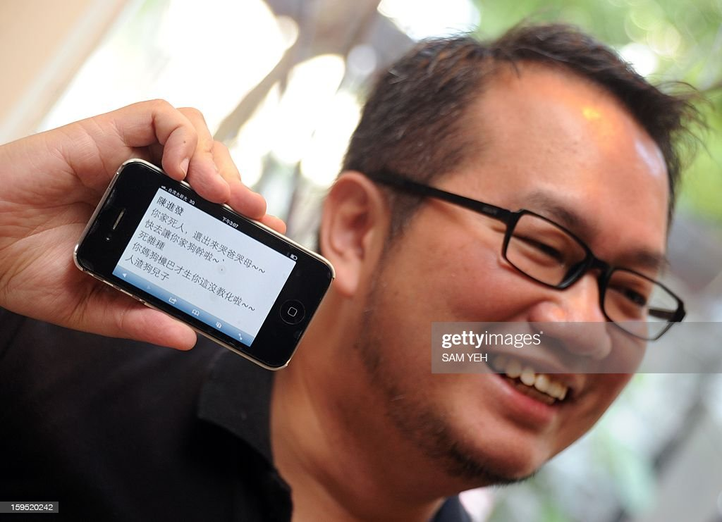 Chen Ching-hsueh, a Taiwanese gay member, displays a threatening message that was sent to his smart phone, to the press outside the Taipei High Administrative Court on January 15, 2013. Chen said he received death threats after he went public with his appeal against the government in the Taipei High Administrative Court to register his 'marriage' with his gay partner. The court did not make a final decision in a hearing on January 15 on whether to submit Chen's case to the Grand Justices to allow time for both sides to present additional arguments. AFP PHOTO / Sam Yeh