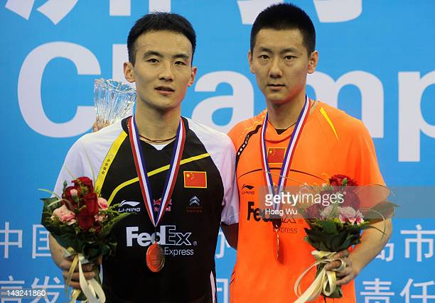 Chen Jin of China poses with Du Pengyu of China after winning the men's singles final during day six of the 2012 Badminton Asia Championships at...