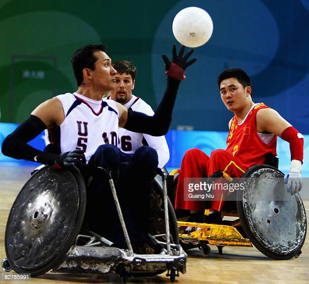 Chen Jun of China watches Will Groulx of USA gets a ball in the Wheelchair Rugby match between USA and China at Beijing Science and Technology...