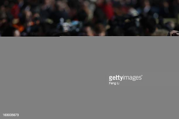 Chen Kaige , Chinese famous film director, walks through a swarm of journalists outside the Great Hall of the People before the opening session of...