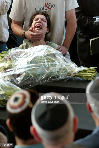 Chen Kinen seated in a wheelchair as she recovers from her wounds from a suicide bombing attack cries out during the joint funeral for her daughter...