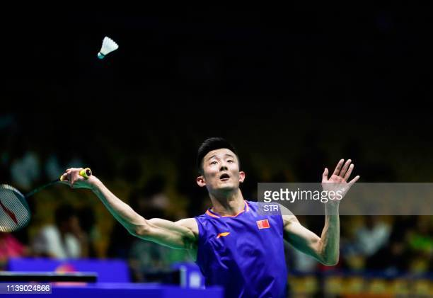 Chen Long of China hits a return against Kanta Tsuneyama of Japan during their men's singles first round match at the 2019 Badminton Asia...