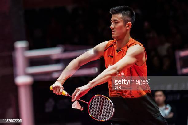 Chen Long of China serves against Viktor Axelsen of Denmark during their men's singles first round match at the BWF World Tour Finals badminton...