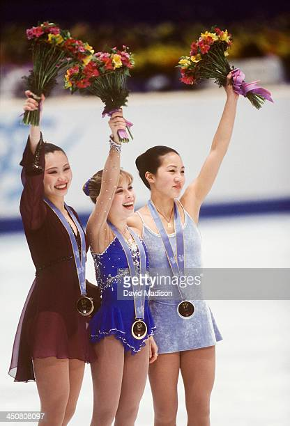 Chen Lu Tara Lipinski and Michelle Kwan wave to the crowd during the awards ceremony for the Ladies Singles event of the figure skating competition...