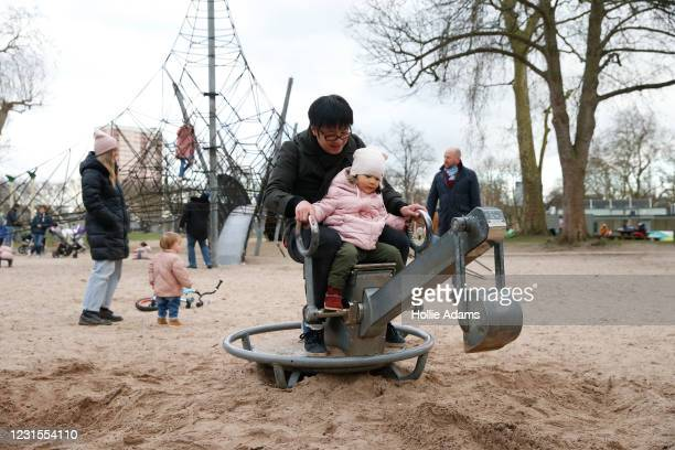 Chen Meng playing in the sand with his daughter Yimeng 2, at Victoria Park playground on March 6, 2021 in London, England. Londoners are enjoying...