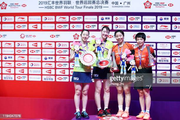 Chen Qing Chen and Jia Yi Fan of China and Mayu Matsumoto and Wakana Nagahara of Japan react with trophy during the award ceremony after their...
