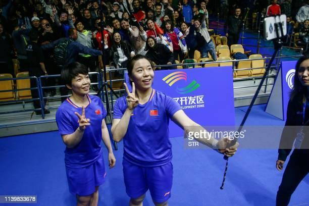 Chen Qingchen and Jia Yifan of China take a selfie after winning the women's doubles final against Mayu Matsumoto and Wakana Nagahara of Japan at the...