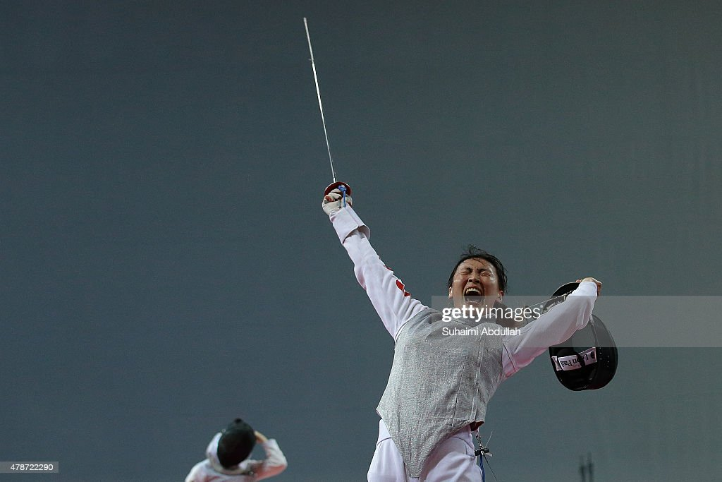 Chen Qinghui of China (R) celebrates victory over Wong Nicole Mae Hui Shan of Singapore in the women's individual foil round of 32 during the 2015 Asian Fencing Championships at OCBC Arena on June 27, 2015 in Singapore.