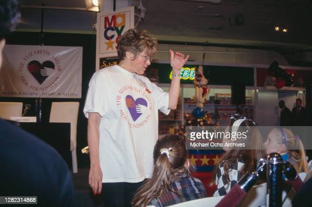 Chen Sam , Elizabeth Taylor's publicist, wearing a white t-shirt with the logo of the 'Elizabeth Taylor AIDS Foundation', which also appears on a...
