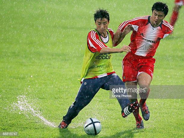 Chen Tao and Zhou Haibin of the Chinese National Football Team, take part in training in rain during a practice session for the East Asian Football...
