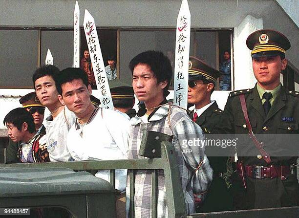 Chen Wenjian stands beside a police officer moments before his execution 10 January 1996 in Zhongshan in Zhongshan Chen was one of 14 who assaulted a...