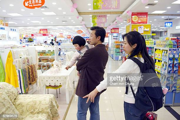 Chen Xiangjian holds his daughter while shopping with his wife at a department store on March 25, 2005 in Chongqing, Sichuan province in southwest...