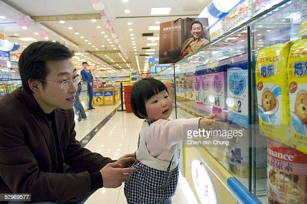 Chen Xiangjian shops for baby formula with his daughter at a department store on March 25 2005 in Chongqing Sichuan province in southwest China...