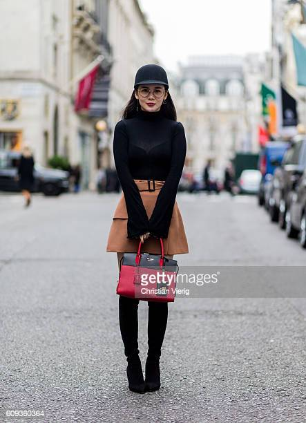 Chen Xiaxue wearing a black long shirt cap glasses a mini skirt and overknees and a red black Prada bag outside Marques Almeida during London Fashion...