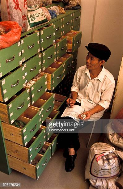 Chen YiHe Chinese Herbalist studying the inventory of his remedies and potions in his clinic Xiao Meng Yang town Yunnan province China