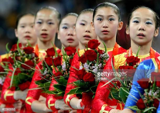 Cheng Fei Deng Linlin He Kexin Jiang Yuyuan Li Shanshan and Yang Yilin of the Chinese women's gymnastics team look on after winning the gold medal...