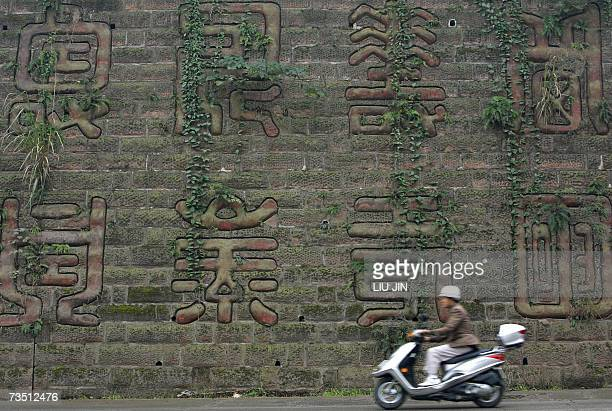 A villager rides a scooter past an ancient wall engraved with Chinese characters 07 March 2007 in the outskirts of Chengdu in China's southwestern...