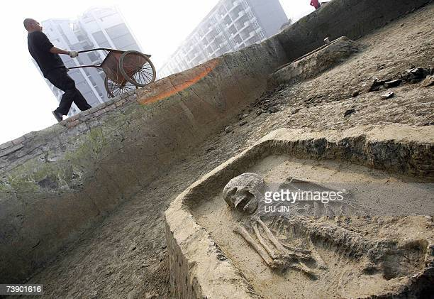 A worker pushes a cart pass the grave chamber at the excavation site near the Jinsha Museum in Chengdu southwest China's Sichuan province 07 February...