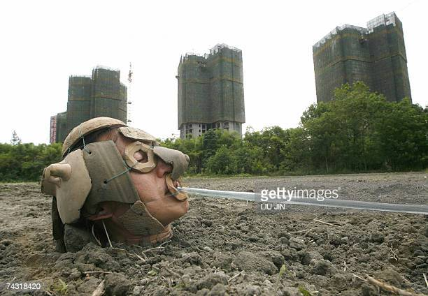 Local performance artist Yin Xiaofeng, 42-year old, wearing the helmets made by various unearthed pottery pieces from Chinese ancient dynasties,...