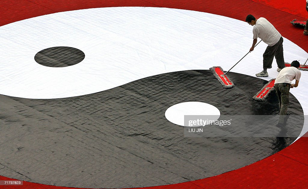 Workers clean a ying and yang symbol upon the closing ceremony of the second China Taoism Culture festival in Chengdu, China's southwestern province of Sichuan, 29 August 2006. The ancient chinese art of tai chi chuan is believed to have many health benefits and and can also be used for self defense. AFP PHOTO/ LIU Jin