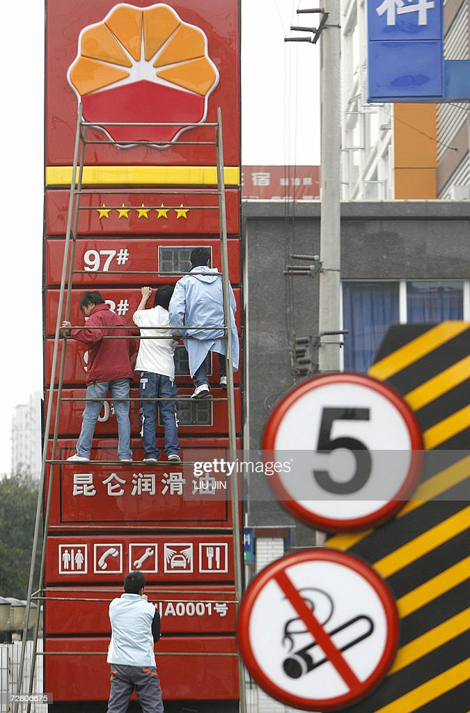 Workers install a price board at a gas station that belongs to