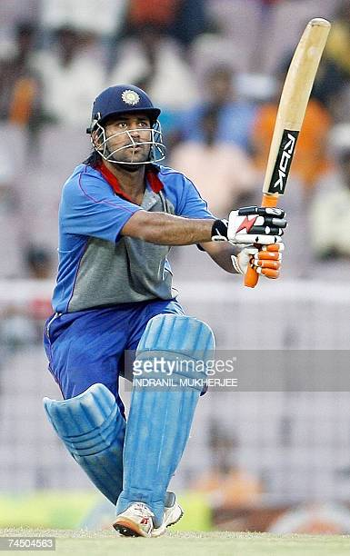 Asian XI cricketer Mahendra Singh Dhoni watches a ball to the boundary after playing a shot on way to his century during the third One Day...