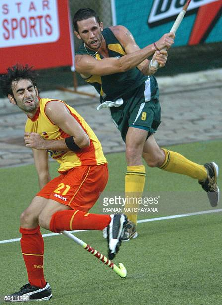 Spanish field hockey player Eduard Arbos takes evasive action as Australian Mark knowles hits the ball during their match in the Champions Trophy in...