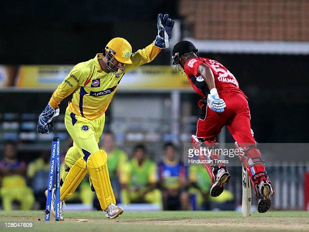 Chennai Super Kings captain MS Dhoni raises his hand in confidence as Trinidad Tobago batsman Lendl Simmons is run out by Wriddhiman Saha during the...