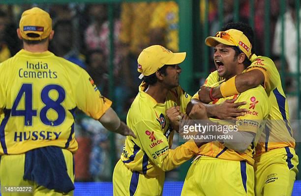 Chennai Super Kings fielder Suresh Raina celebrates the wicket of Mumbai Indians batsman Harbhajan Singh with his teammate during the IPL Twenty20...