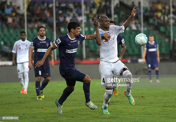 Chennaiyin FC defender Eder Monteiro vies for the ball with FC Pune City's forward Dramane Traore during the Indian Super League football match...