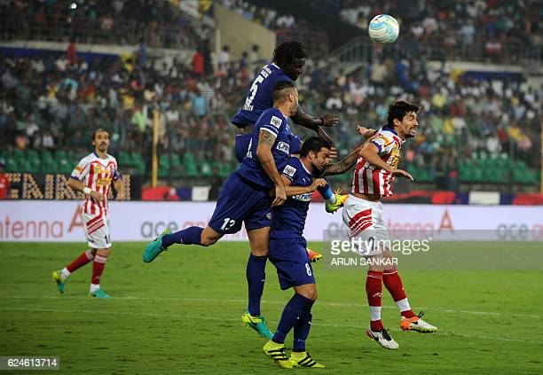 Chennaiyin FC defenders Bernard Mendy Eli Sabia Filho and midfielder Manuele Blasi vie for the ball with Atletico De Kolkata defender Herique Fonseca...
