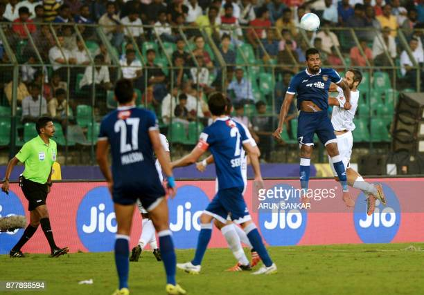 Chennaiyin FC Dhanapal Ganesh jumps for the ball with NorthEast United FC Adilson Goiano during the Indian Super League football league match between...