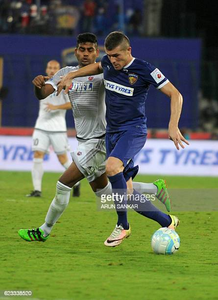 Chennaiyin FC Forward Davide Succi vies for the ball with FC Pune City's defender Augustin Fernandes during the Indian Super League football match...