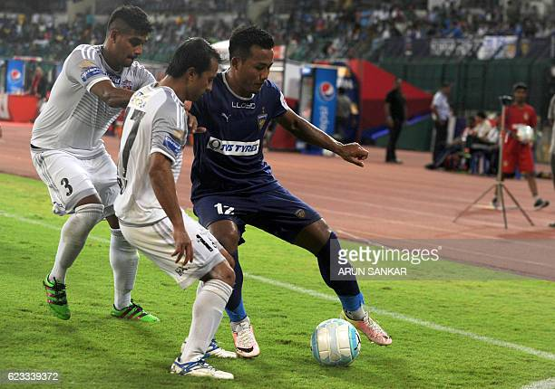 Chennaiyin FC' forward Jeje Lalpekhlua vies for the ball with FC Pune City's defenders Augustin Fernandes and Yamnam Raju during the Indian Super...