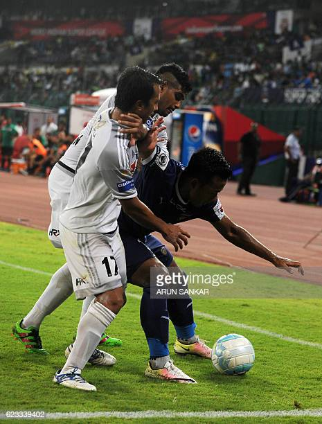 Chennaiyin FC forward Jeje Lalpekhlua vies for the ball with FC Pune City's defender Augustin Fernandes and Yamnam Raju during the Indian Super...