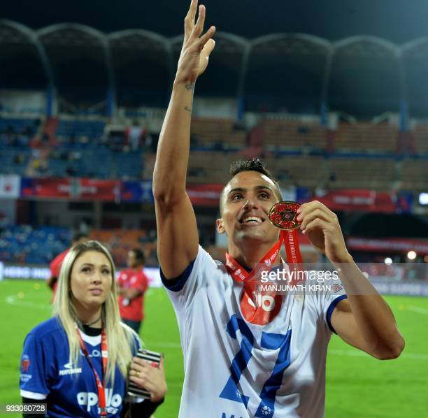 Chennayin FC player Mailson Alves gestures towards fans while his girlfriend looks on after the team's 32 victory against Bengaluru FC in the final...